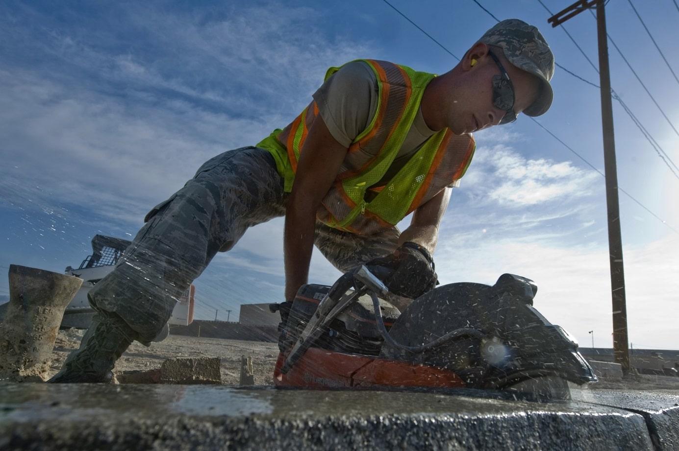 Un ouvrier qui s'abaisse pour ramasser des outils de travail