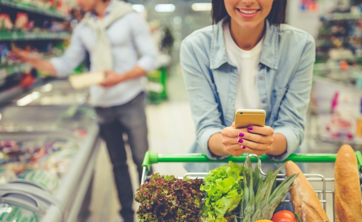 Consultation de son appareil mobile au supermarché